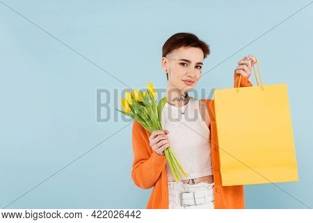 Young Tattooed Woman In Orange Cardigan Holding Yellow Tulips And Shopping Bag Isolated On Blue.