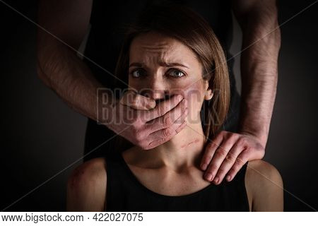 Man Abusing Scared Woman On Black Background. Domestic Violence