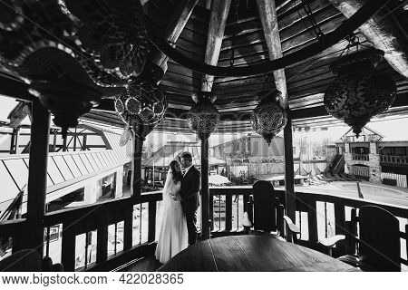 Black And White Photo. The Bride And Groom Stand In A Retro Gazebo.