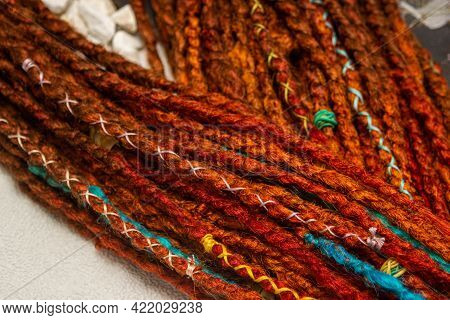 Braided Colored Pigtails As A Background. Bright Braided Braids. Handmade