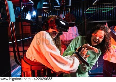 Excited African American Girl Taking Photo Of Astonished Girl In Vr Headset.
