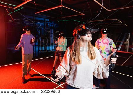 Astonished Teenage Girl Gaming In Vr Headset Near Multiethnic Friends.