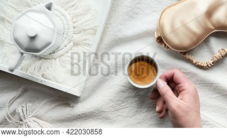 Espresso In Hand, Tray With White Ceramic Espresso Coffee Maker On Trendy Macrame Pad. Sleep Mask On