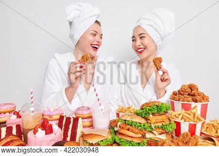 Joyful Young Diverse Women Looks Gladfully At Each Other Have Fun And Eat High Calorie Harmful Food
