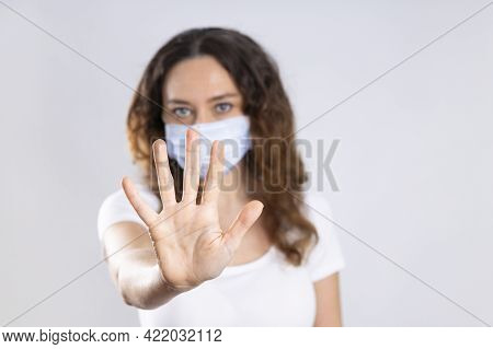 Young Woman Holding Up Her Hand To Stop A Disease Isolated On White