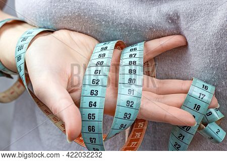Caucasian Woman Hand Holding The Measuring Tape With The 90-60-90 Centimeters On It. The Ideal Woman