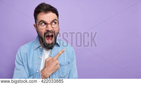 Irritated Outraged Bearded Man Screams Loudly Opens Mouth Points At Upper Right Corner Being Annoyed