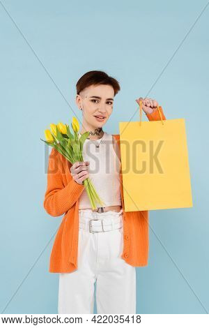 Happy Woman With Tattoos In Orange Cardigan Holding Yellow Tulips And Shopping Bag Isolated On Blue.