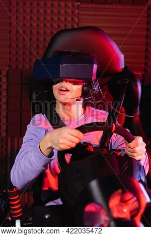 Astonished Teenager In Vr Headset Racing On Car Simulator.