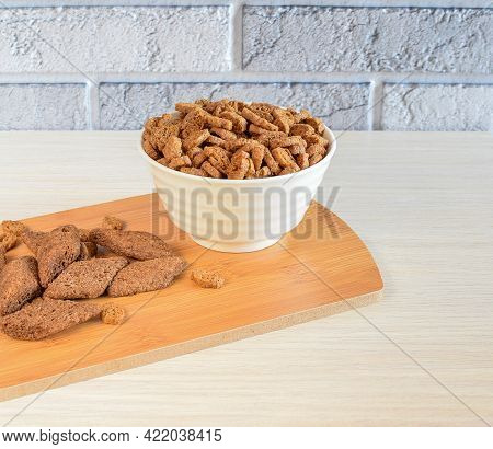 Crispy Appetizing Croutons In A White Plate On A Wooden Kitchen Board, Against A Brick Wall Backgrou