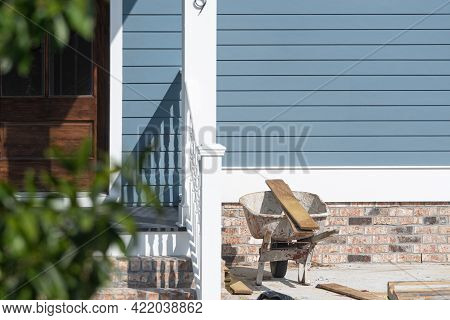 Wheel Barrow And Wooden Boards In Front Of Newly Constructed House
