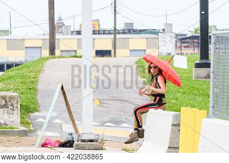 New Orleans, La - May 9: Woman In Colorful Pant Suit Sits On Concrete Barricade Holding An Umbrella