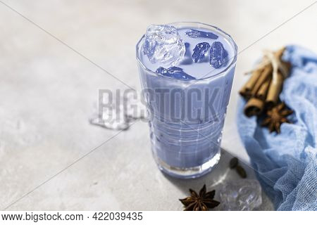 Blue Matcha Latte In Glass On Light Concrete Background. Cold Blue Thai Tea With Ice With Milk.
