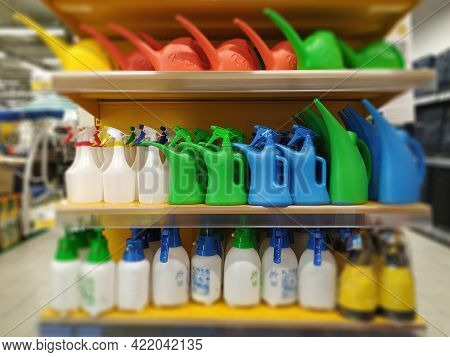 Shop Shelves With Colored Watering Cans For The Garden And Vegetable Garden. Plant Care Products.