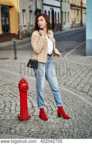 Young Woman Wearing Red Knitted Fabric Block Heel Sock Shoes And Blue Denim Jeans Pants Standing Nea
