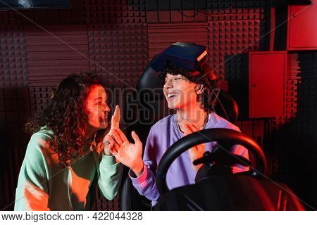 Teenage Guy On Car Racing Simulator Talking To Cheerful African American Friend.