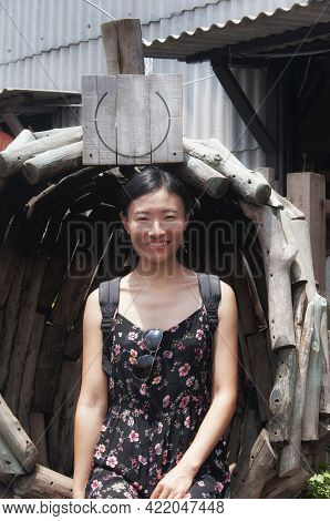 A Smiling Chinese Woman Sitting On A Wooden Chair On The Historic Chew Jetty In The Georgetown Area
