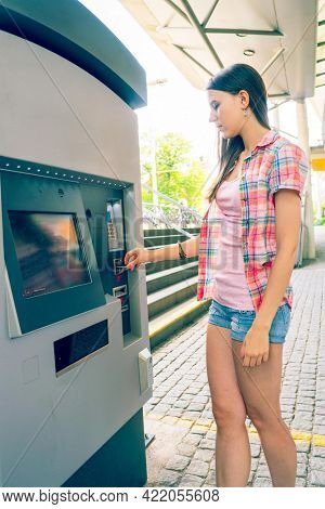 Young woman uses a vending machine for transport tickets