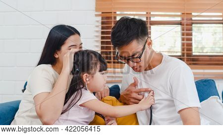 Happy Cheerful Asian Family Dad, Mom And Daughter Playing Funny Game As Doctor Having Fun On Sofa At