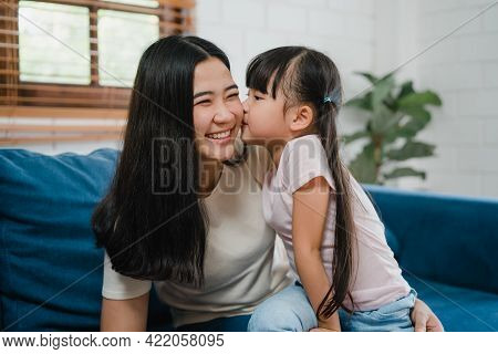 Happy Asian Family Mom And Daughter Embracing Kissing On Cheek Congratulating With Birthday At House