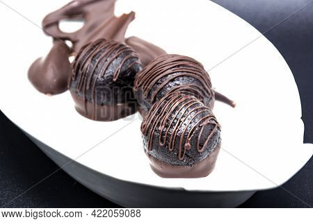 Chocolate Truffles In White Plate On Black Background Table. Homemade Dark Chocolate Bitter Truffles