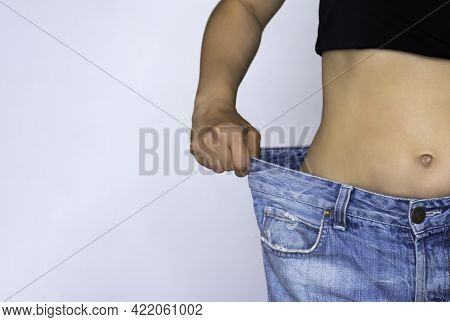 A Slim Woman Shows Off Her Weight Loss By Wearing Jeans. Weight Loss Concept