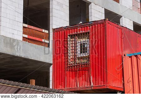 Temporary Housing For Construction Workers Made From A Red Container. A Window With Bars Against Thi