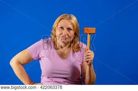 Pretty Middle Aged Woman Posing With A Kitchen Wooden Mallet Isolated On Blue Studio Background. War