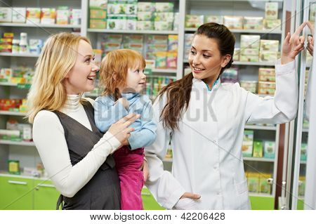 Cheerful pharmacist chemist woman demonstrating vitamins to child girl in pharmacy drugstore poster