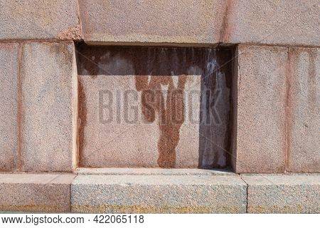 A Small Square Alcove In A Red Granite Wall. Water Flows. Limestone Traces.