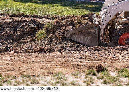 Small Bulldozer Digging In Yard For Pool Installation.