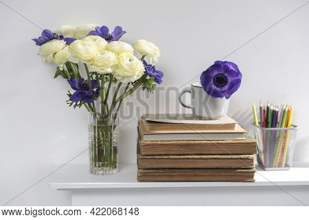 One Blue Anemone In A Cup In The Style Of The Seventies On The Table With Pile Ofbooks As An Interio