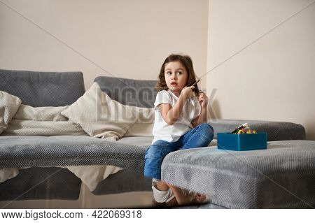 Cute Little Girl Combing Her Hair With A Wooden Comb While Sitting On The Sofa In The Living Room. D