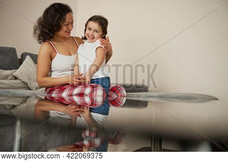 Loving Mother Sits On The Sofa And Tenderly Hugs Her Beautiful Smiling Baby Girl. Happy Childhood An