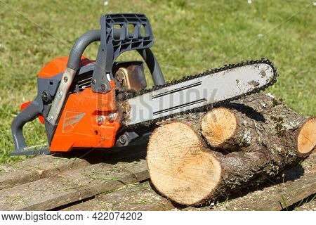 Chainsaw And Lumber In Outdoors With Green Grass In Background