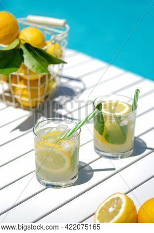 Homemade Lemonade In Glasses With Lemon Slice, Basket Of Lemons, Drinking Straw, On White Table, In