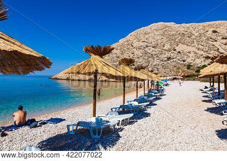 Stara Baska, Croatia - July, 21: Straw Umbrellas In The Beautiful Oprna Beach On July 21, 2020