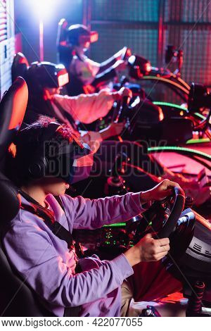 Teenagers In Vr Headsets Racing On Car Simulators On Blurred Background.