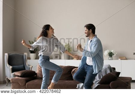 Overjoyed Multiracial Couple Dance Together At Home