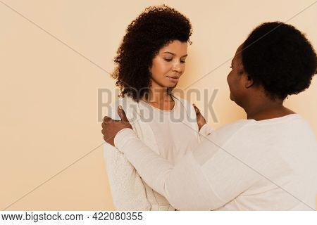 African American Middle Aged Mother Supporting Sad Adult Daughter With Hands On Shoulders Isolated O