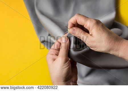 Seamstress's Hands On Yellow Tendy Background. Female Hands With A Needle, Thread And Thimble. Woman
