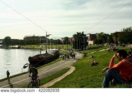 Krakow, Poland - June 7, 2009: People Relaxing, Sitting, Walking And Laying On The Grass By The Rive