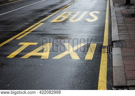Bus Stop With A Road Marking Indicating A Bus And Taxi Lane On A Newly Ashphalted Street In A City U