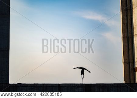 Silhouette Of Flexible Girl Dong Handstand In Split On Sky Background. Concept Of Individuality, Cre