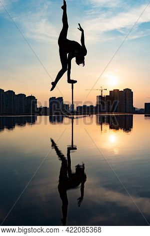 Silhouette Of Flexible Acrobat Doing Handstand On The Dramatic Sunset And Cityscape Background. Conc