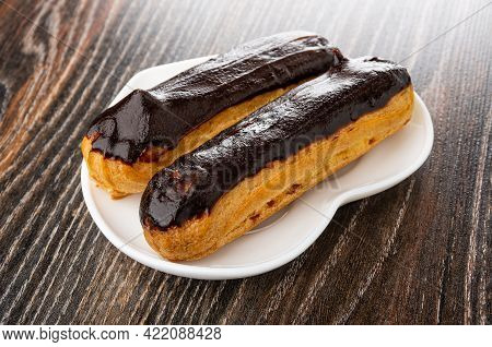 Two Eclairs With Chocolate Glaze In Heart Shape Plate On Dark Wooden Table