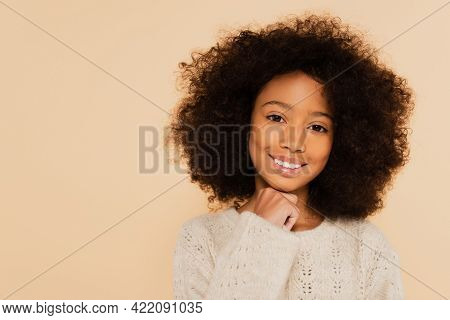 Portrait Of Smiling Preteen African American Girl With Hand Near Face Isolated On Beige.