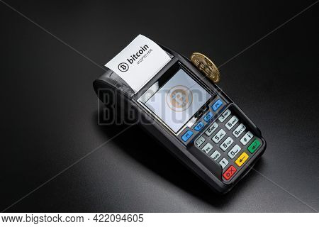 Payment Terminal Ready To Accept Bitcoins For Payment On The Black Table. Bitcoin Gold Coin Sticks O