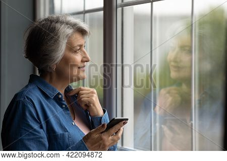 Middle Aged Woman Holding Cellphone Standing Near Window Looking Outside