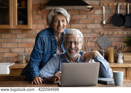 Mature Spouses Family Spend Time Together In Kitchen With Laptop